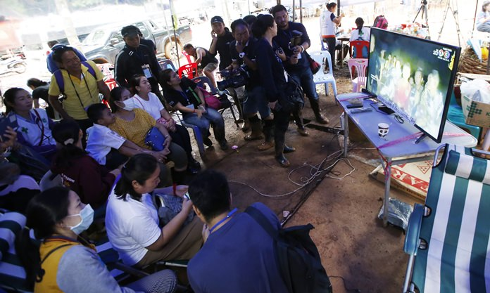 Family members of the 12 boys and their soccer coach watch a video clip of 12 boys on television after they were found alive, in Mae Sai, Chiang Rai province, in northern Thailand, Wednesday, July 4, 2018. Rescuers found all 12 boys and their soccer coach alive deep inside a partially flooded cave in northern Thailand.(AP Photo/Sakchai Lalit)
