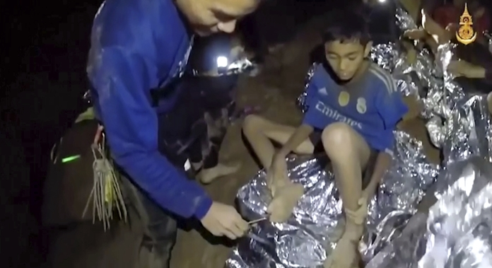 In this July 3, 2018, image taken from video provided by the Royal Thai Navy Facebook Page, a Thai Navy SEAL medic helps an injured child inside a cave in Mae Sai, northern Thailand. (Royal Thai Navy Facebook Page via AP)