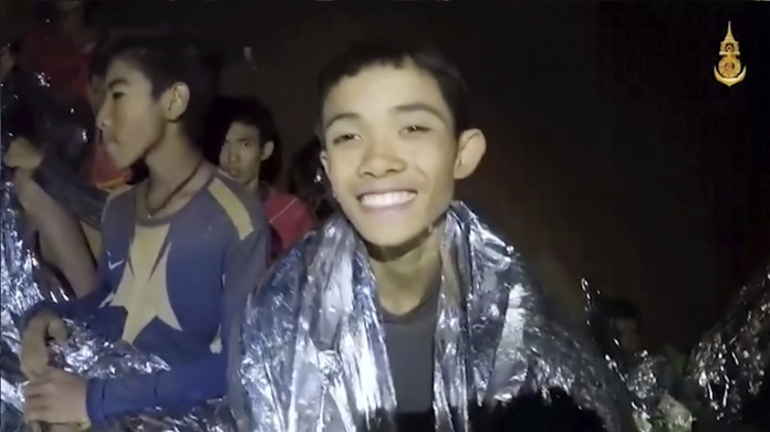 In this July 3, 2018, image taken from video provided by the Royal Thai Navy Facebook Page, a Thai boy smiles as Thai Navy SEAL medic help injured children inside a cave in Mae Sai, northern Thailand. (Royal Thai Navy Facebook Page via AP)
