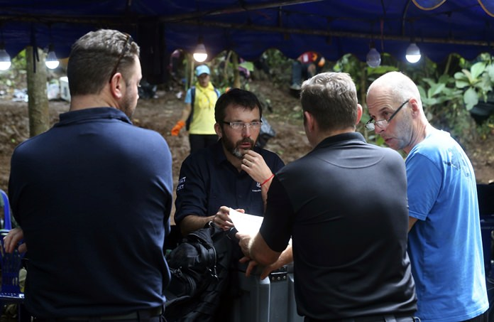 Australian Federal Police and Defense Force personnel talk each other near a cave where 12 boys and their soccer coach are trapped, in Mae Sai, Chiang Rai province, in northern Thailand, Thursday, July 5, 2018. With more rain coming, Thai rescuers are racing against time to pump out water from a flooded cave before they can extract 12 boys and their soccer coach with minimum risk, officials said Thursday. (AP Photo/Sakchai Lalit)