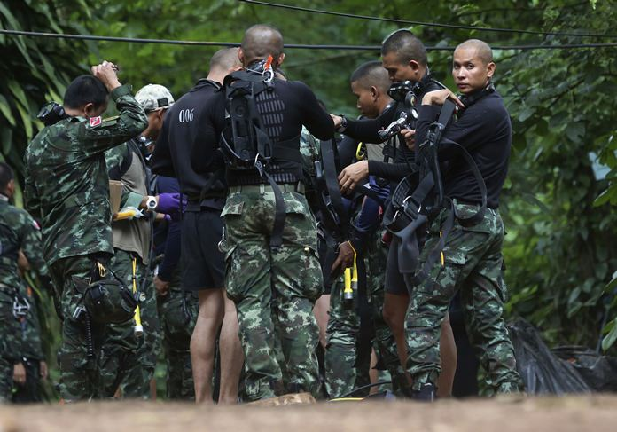 Rescuers prepare dive gear at the entrance of a cave complex where 12 boys and their soccer coach are trapped inside in Mae Sai, Chiang Rai province, in northern Thailand, Wednesday, July 4, 2018. (AP Photo/Sakchai Lalit)