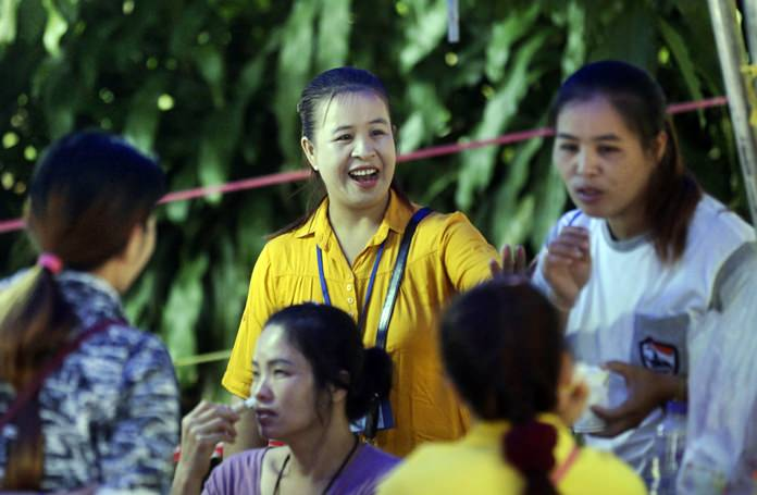 Family members talk together while waiting near a cave where 12 boys and their soccer coach are trapped, in Mae Sai, Chiang Rai province, in northern Thailand, Thursday, July 5, 2018. A Thai official overseeing the rescue operation of the soccer team trapped in the flooded cave said they may not all be extracted at the same time depending on their health. (AP Photo/Sakchai Lalit)