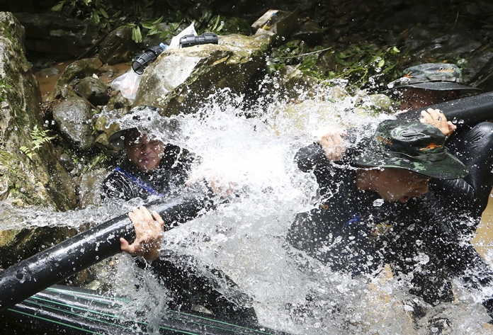 1. Thai soldiers try to connect water pipes that will help bypass water from entering a cave where 12 boys and their soccer coach have been trapped since June 23, in Mae Sai, Chiang Rai province, in northern Thailand Saturday, July 7, 2018. Thai authorities are racing to pump out water from the flooded cave before more rains are forecast to hit the northern region. (AP Photo/Sakchai Lalit)
