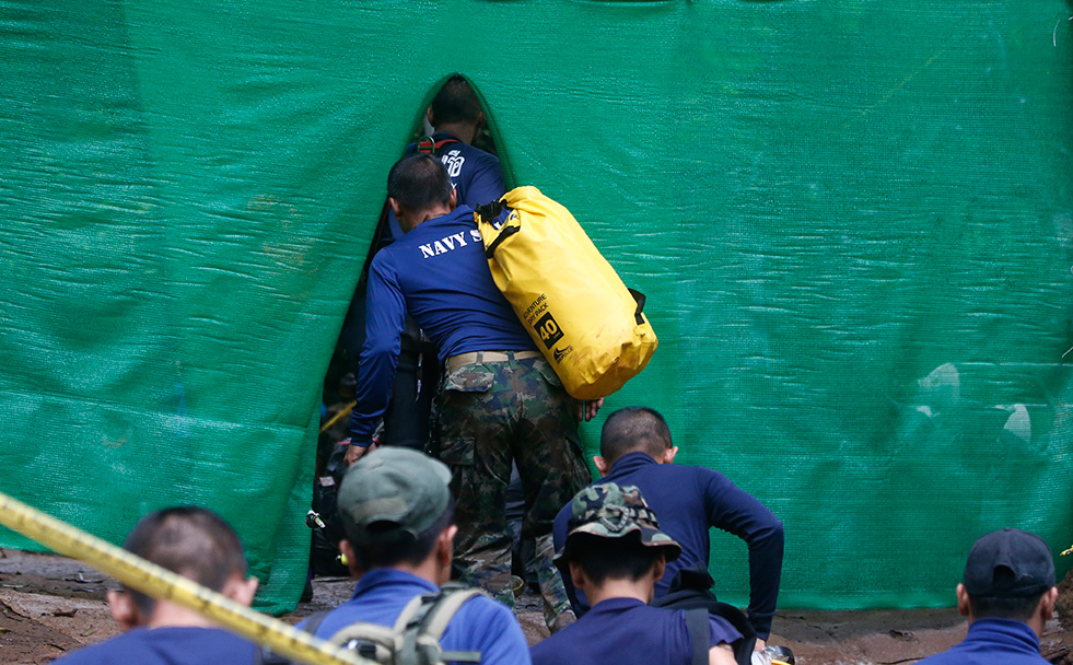 Rescuers arrive near cave where 12 boys and their soccer coach have been trapped since June 23, in Mae Sai, Chiang Rai province, in northern Thailand Sunday, July 8, 2018. (AP Photo/Sakchai Lalit)