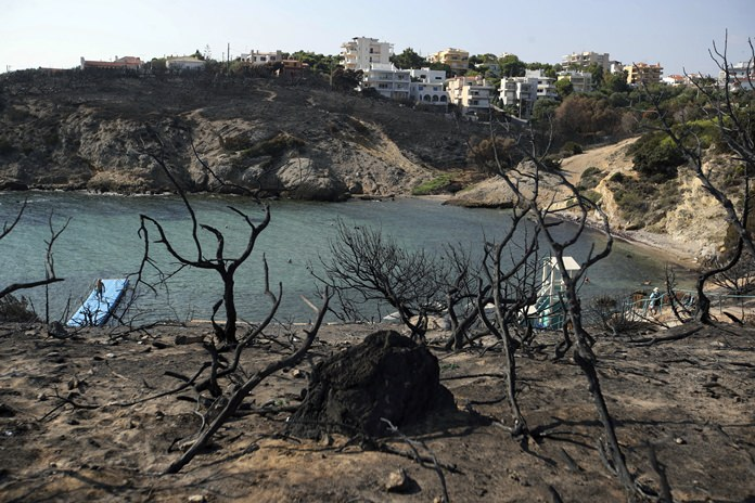 People swim at a beach in Rafina, east of Athens, Wednesday, Aug. 1, ten days after a wildfire in the area killed at least 87 people. (AP Photo/Thanassis Stavrakis)