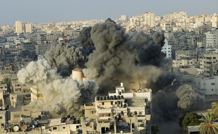 Smoke rises from an explosion caused by an Israeli airstrike on a building of Said al-Mis'hal cultural center in Gaza City, Thursday, Aug. 9. (AP Photo/Arafat Kareem)