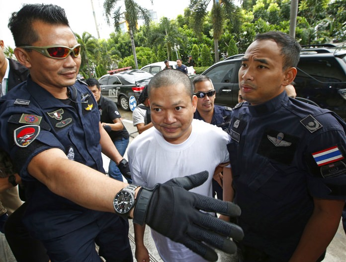 In this Thursday, July 20, 2017, file photo, ex-monk Wirapol Sukphol is escorted by the Department of Special Investigation officials to the prosecutor's office in Bangkok. (AP Photo/Sakchai Lalit)