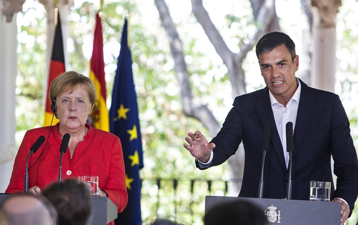 Spanish Prime Minister Pedro Sanchez, right, speaks during a joint news conference with German Chancellor Angela Merkel at the Guzmanes Palace in Sanlucar de Barrameda, southern Spain Saturday Aug. 11. (AP Photo/Javier Fergo)