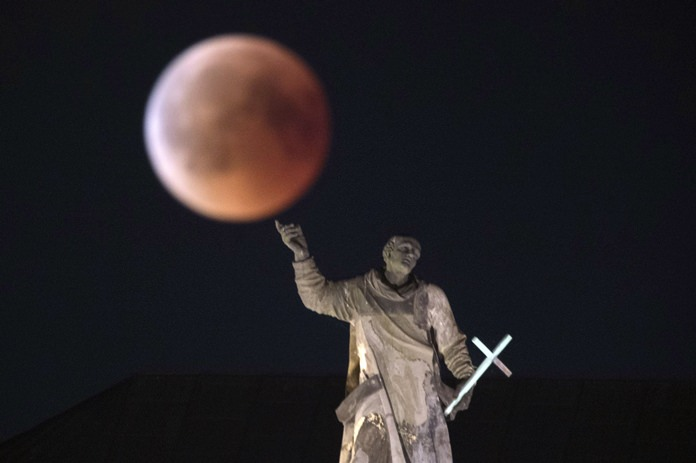 The moon turns red during a total lunar eclipse, as seen from Dresden, Germany, Friday, July 27, 2018. (Sebastian Kahnert/dpa via AP)