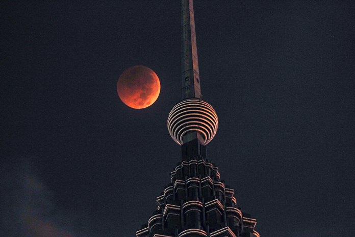 A full moon sets over the Petronas Twin Towers during a complete lunar eclipse in Kuala Lumpur, Malaysia, Saturday, July 28, 2018. (AP Photo/Yam G-Jun)