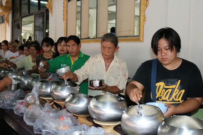 Believers perform a Tak Bat ceremony at Wat Suttawas on Asalaha Bucha Day.