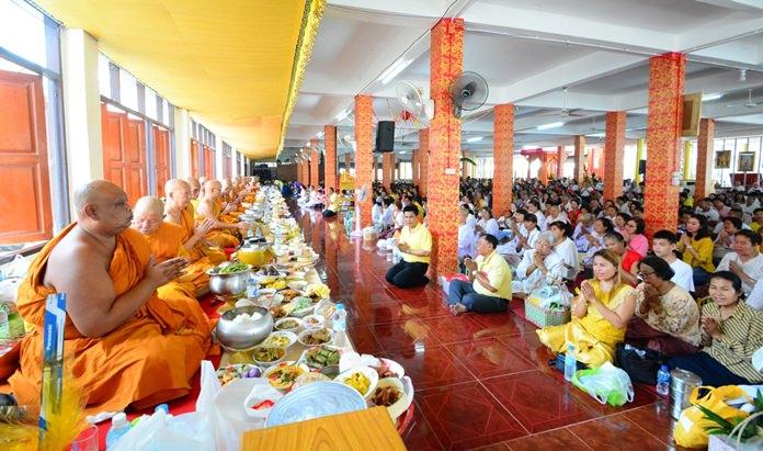 Devout Buddhists present alms at Wat Boonsamphan.