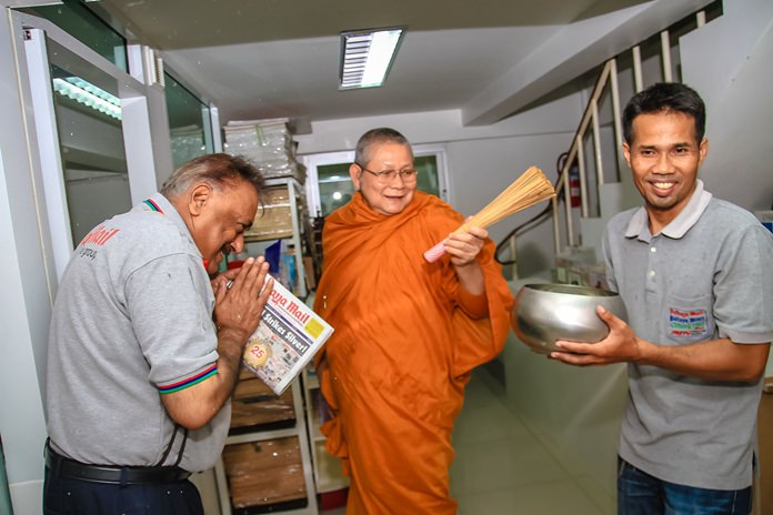 Peter Malhotra and Thepporn Donvithai receive blessings as Phra Khru Sangkharaksa Monthon Sumano sprinkles holy water around our offices.