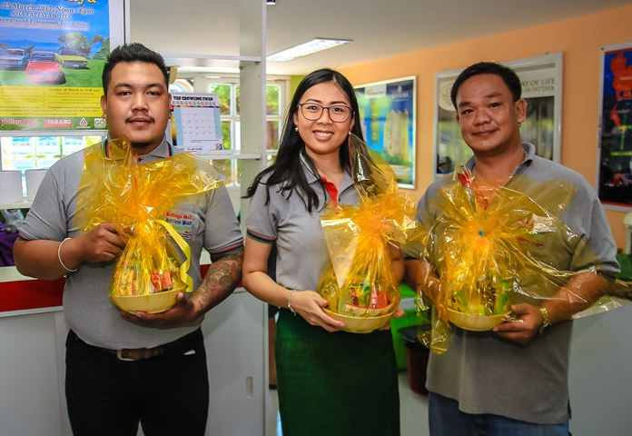 Krisada Kongdee, Nutsara Duangsri and Thanawat Suansook prepare packages of daily essentials for offering to the monks.
