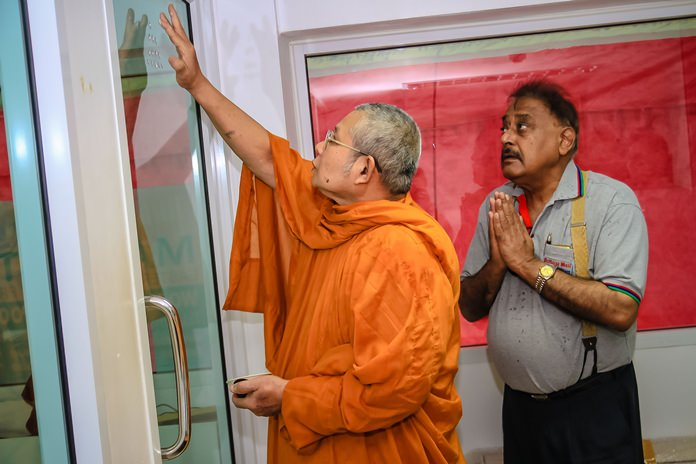 Pratheep Malhotra in deep contemplation as the revered head monk anoints his office with holy markings.