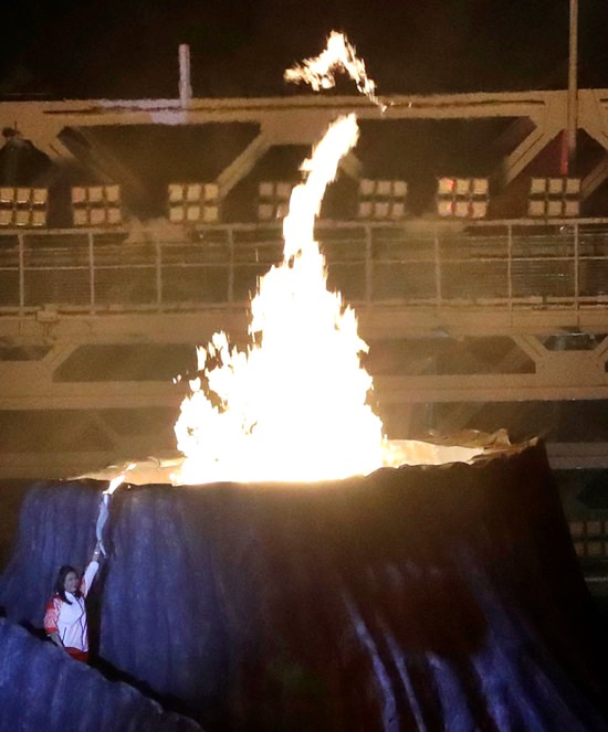 The cauldron is lit by former Olympic badminton gold medalist Susi Susanti from Indonesia (bottom left) during the opening ceremony for the 18th Asian Games in Jakarta. (AP Photo/Lee Jin-man)
