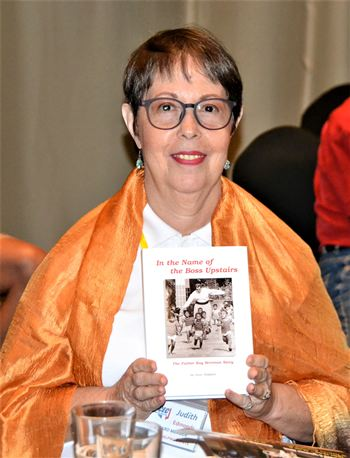 """During the Open Forum portion of the meeting, Member Judith Edmonds announced she still has books available for sale with the proceeds going to the Pattaya Orphanage. Here she displays a copy of the biography of Father Ray Brennan, founder of the Orphanage, titled """"In the Name of the Boss Upstairs."""""""