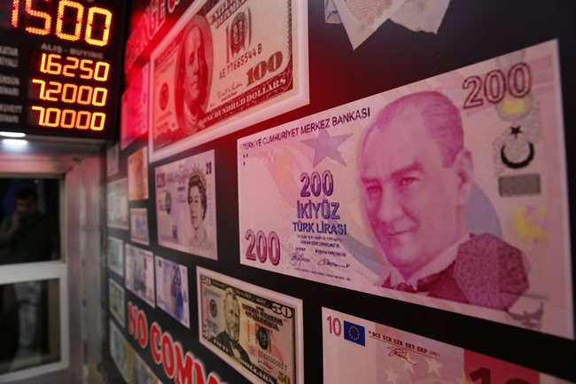 An oversized copy of a 200 Turkish lira banknote, featuring a photo of modern turkey's founder Mustafa Kemal Ataturk decorates a currency exchange shop in Istanbul, Monday, Aug. 13. (AP Photo/Lefteris Pitarakis)