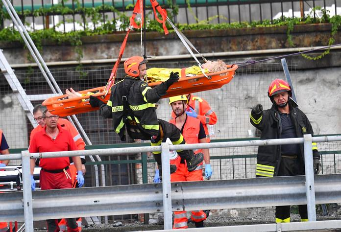 Rescuers recover an injured person after the Morandi highway bridge collapsed in Genoa, northern Italy, Tuesday, Aug. 14. (Luca Zennaro/ANSA via AP)