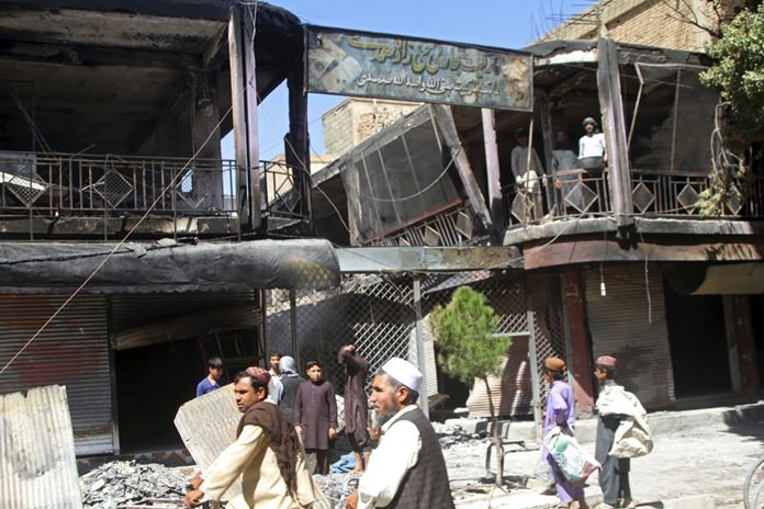 Afghan men stand in front of burned out shops following a Taliban attack in Ghazni, Afghanistan, Wednesday, Aug. 15. (AP Photo/Rahmatullah Nikzad)