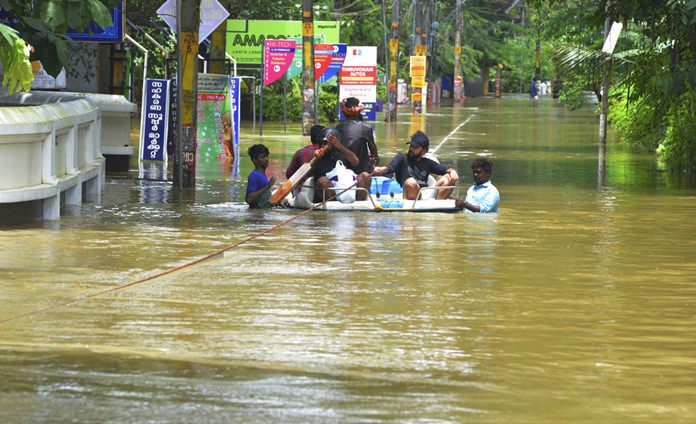People move past a flooded area in Thrissur, in the southern Indian state of Kerala, Friday, Aug. 17. (AP Photo)
