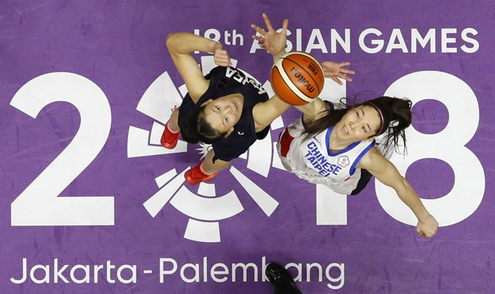 Combined Koreas Ro Suk Yong, left, and Taiwan's Hsile Bao jump for ball possession during their women's basketball match at the 18th Asian Games in Jakarta, Indonesia on Friday, Aug. 17. (AP Photo/Aaron Favila)