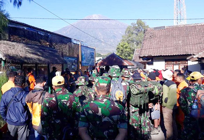 In this July 30, 2018, file photo, Indonesian soldiers and rescue teams gather to prepare for evacuating tourists from Mount Rinjani, seen in the background, at Sembalun in East Lombok, Indonesia. (AP Photo)
