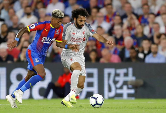 Crystal Palace's Patrick van Aanholt, left, duels for the ball with Liverpool's Mohamed Salah during the English Premier League soccer match between Crystal Palace and Liverpool at Selhurst Park stadium in London, Monday, Aug. 20. (AP Photo/Kirsty Wigglesworth)