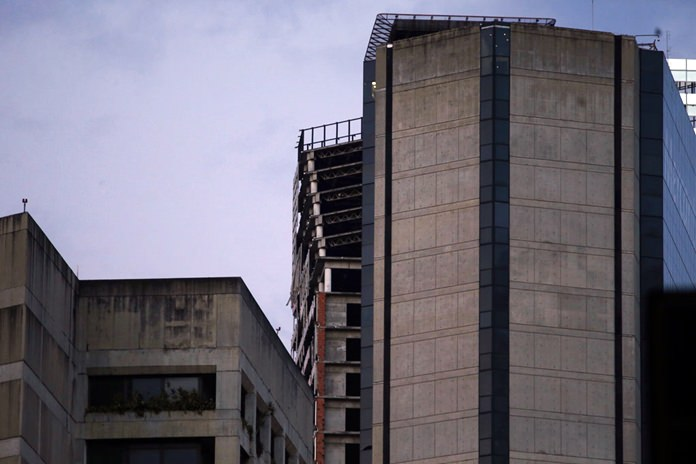 """An abandoned, unfinished skyscraper known as """"The Tower of David"""" shows an inclination on the top floors where the columns are exposed after a powerful earthquake shook eastern Venezuela, causing buildings to be evacuated in the capital of Caracas, Tuesday, Aug. 21. (AP Photo/Ariana Cubillos)"""