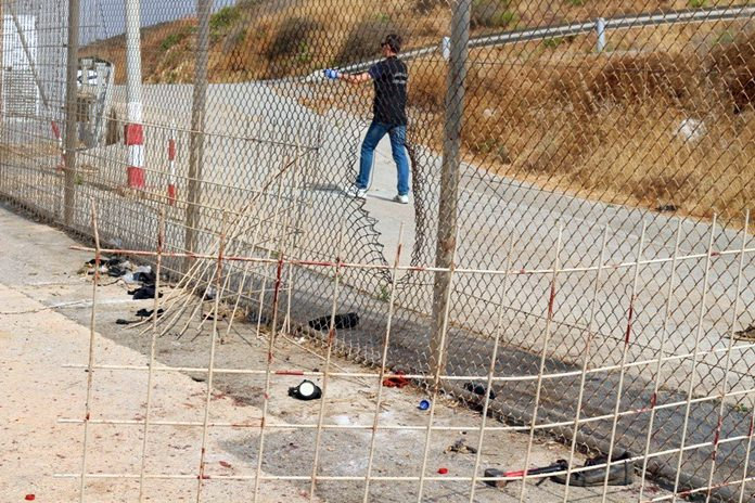 A fence dividing the Spanish enclave of Ceuta and Morocco is seen damaged in this image released by the Spanish Guardia Civil on Wednesday Aug. 22. (Guardia Civil via AP)
