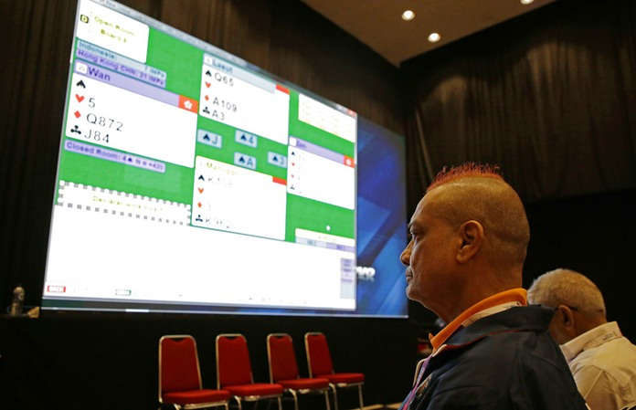 In this Aug. 21, 2018, photo, India's bridge player Finton Lewis watches a bridge match competition on a screen at the 18th Asian Games in Jakarta, Indonesia. (AP Photo/Firdia Lisnawati)