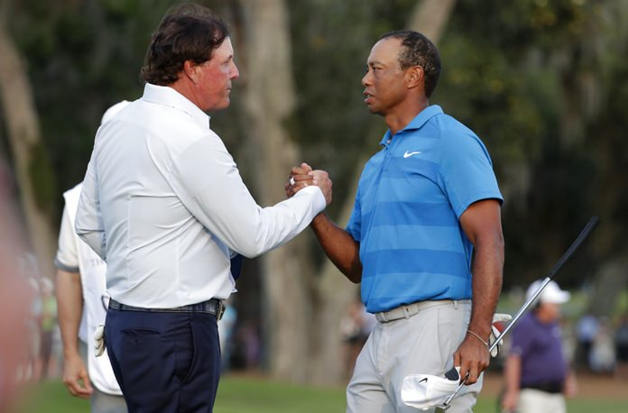 In this May 10, 2018, file photo, Phil Mickelson, left, and Tiger Woods shake hands after the first round of the Players Championship golf tournament, in Ponte Vedra Beach, Fla. (AP Photo/Lynne Sladky)