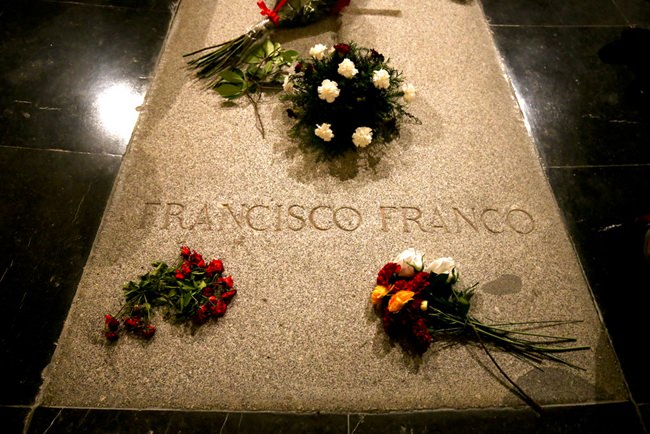 Flowers are placed on the tomb of former Spanish dictator Francisco Franco inside the basilica at the the Valley of the Fallen monument near El Escorial, outside Madrid, Friday, Aug. 24. (AP Photo/Andrea Comas)
