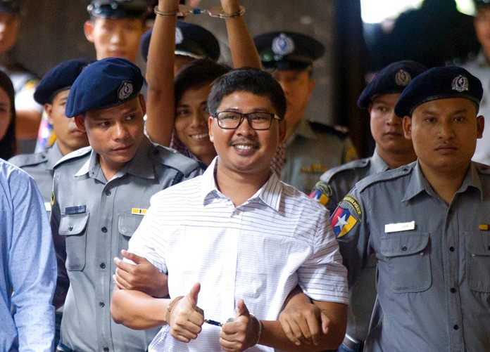 Two Reuters journalists Wa Lone, center, and Kyaw Soe Oo, center back, gestures while being escorted by police upon arrival at a court Monday, Aug. 27, in Yangon, Myanmar. (AP Photo/Thein Zaw)