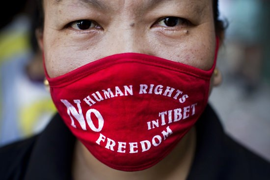 In this Sept. 17, 2014, file photo, an Exile Tibetan woman in New Delhi, India wears a mask during a protest to highlight Chinese control over Tibet. (AP Photo/Bernat Armangue)