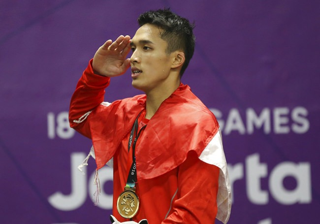 Jonatan Christie of Indonesia salutes to the national flag during the medal ceremony for the men's singles badminton at the 18th Asian Games in Jakarta, Indonesia, Tuesday, Aug. 28. (AP Photo/Achmad Ibrahim)