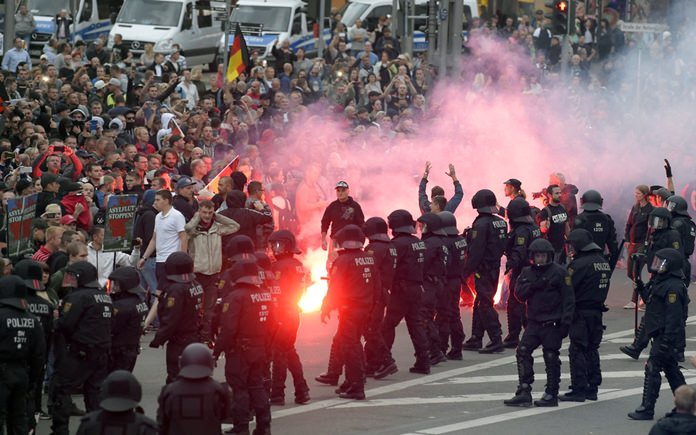 """In this Aug 27, 2018 file photo protesters light fireworks during a far-right demonstration in Chemnitz, Germany, after a man has died and two others were injured in an altercation between several people of """"various nationalities"""" in the eastern German city of Chemnitz on Sunday. (AP Photo/Jens Meyer, file)"""