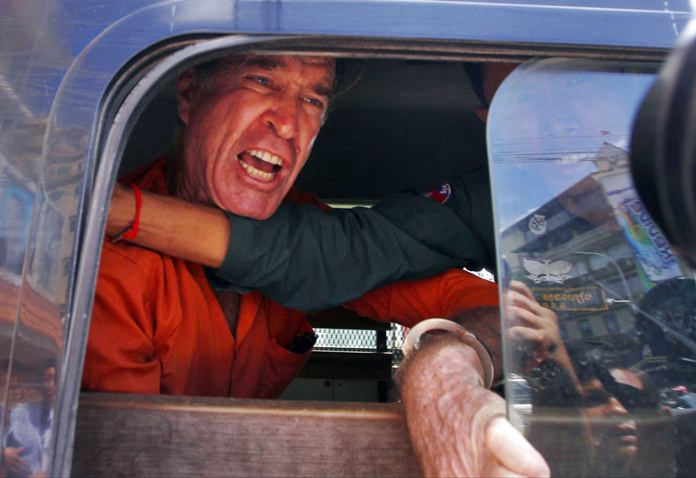 Australian filmmaker James Ricketson speaks from a prisoner van outside Phnom Penh Municipal Court, in Phnom Penh, Cambodia, Friday, Aug. 31, 2018. The 69-year-old Australian is at the court to hear his verdict a charge of violating national security. He was convicted of spying and sentenced to six years in prison Friday. (AP Photo/Heng Sinith)