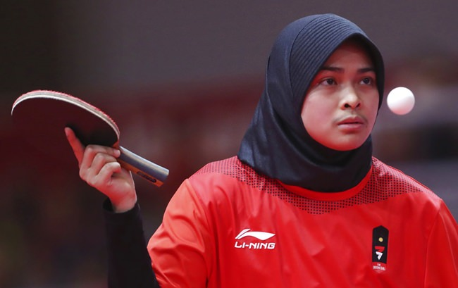 Kharisma Nur Hawwa of Indonesia keeps her eye on the ball against Nitnapha Kongphet of Laos during their women's single table tennis match at the 18th Asian Games in Jakarta, Indonesia, Thursday, Aug. 30, 2018. (AP Photo/Achmad Ibrahim)