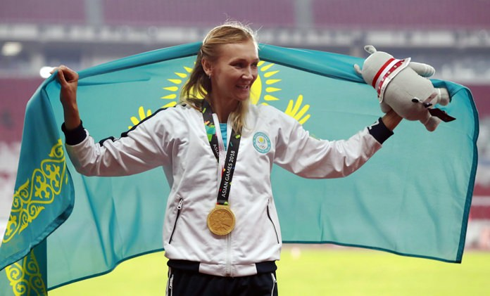Women's triple jump gold medalist Kazakhstan's Olga Rypakova celebrates on the podium during the athletics competition at the 18th Asian Games in Jakarta, Indonesia, Thursday, Aug. 30, 2018. (AP Photo/Bernat Armangue)