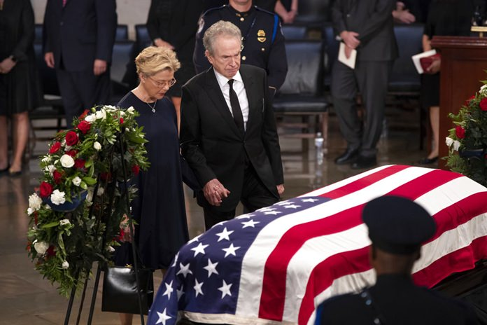 Actors Warren Beatty, right, and his wife Annette Bening, pay their respects at the flag-draped casket of Sen. John McCain of Arizona, who lived and worked in Congress over four decades, in the U.S. Capitol rotunda, Friday, Aug. 31, 2018, in Washington. (AP Photo/J. Scott Applewhite)