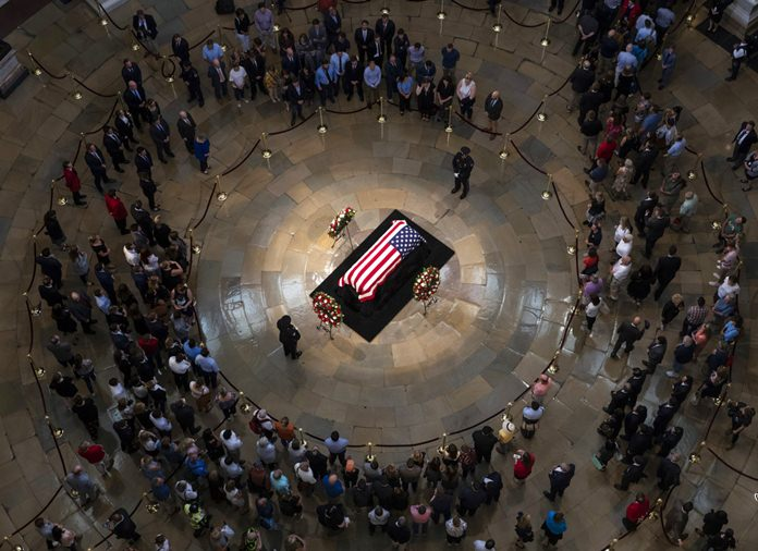 Members of the public walk past the flag-draped casket bearing the remains of John McCain of Arizona, who lived and worked in Congress over four decades, in the U.S. Capitol rotunda in Washington, Friday, Aug. 31, 2018. (AP Photo/J. Scott Applewhite)
