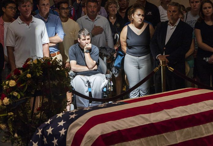 Derek Anderson of Arlington, Va., center, pays his respects, with other members of the public, at the flag-draped casket of John McCain of Arizona, who lived and worked in Congress over four decades, in the U.S. Capitol rotunda in Washington, Friday, Aug. 31, 2018. (AP Photo/J. Scott Applewhite)