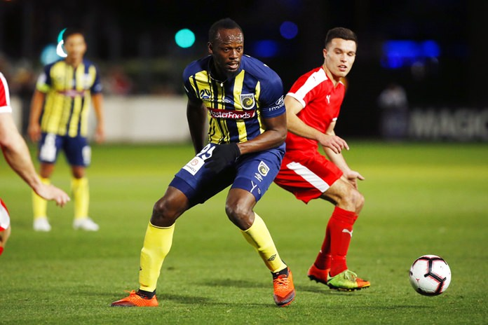 Usain Bolt runs the ball during a friendly trial match between the Central Coast Mariners and the Central Coast Select in Gosford, Australia, Friday, Aug. 31, 2018. Bolt, who holds the world records for the 100- and 200-meter sprints and is an eight-time Olympic gold medalist, is hoping to earn a contract with the Mariners for the 2018-19 season in Australia's top-flight competition. (AP Photo/Steve Christo)