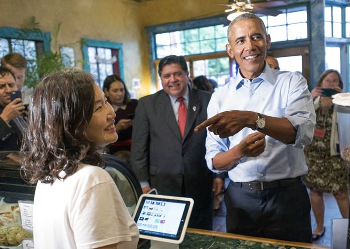 Former President Barack Obama talks with Caffe Paradiso owner Young Jeon during a surprise campaign stop with Illinois Democratic gubernatorial candidate J.B. Pritzker and his running mate, state Rep. Juliana Stratton Friday, Sept. 7, 2018, after speaking on the University of Illinois campus in Urbana, Ill. (Stephen Haas/The News-Gazette via AP)