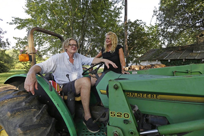 """Tom and Heather LaGarde are seen on Tom's tractor at their home near Saxapahaw, N.C., on Wednesday, Aug. 29, 2018. The LaGardes left New York following the events of 9/11. """"I can't believe how lucky we are to have landed where we did,"""" Heather says. """"I think we were really unmoored by 9/11 ... It changes your perspective on everything. Your priorities change."""" (AP Photo/Gerry Broome)"""