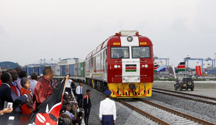 In this May 30, 2017, file photo, Kenyan President Uhuru Kenyatta, 3rd left, watches during the opening of the SGR cargo train runs on a China-backed railway from the port containers depot in Mombasa Kenya, to Nairobi. A wave of Chinese-financed railways and other trade links in Africa and Asia that have prompted worries about debt and Beijing's ambitions is reducing politically dangerous inequality between regions within countries, a multinational group of researchers said Tuesday, Sept. 11, 2018. (AP Photo/Khalil Senosi, File)