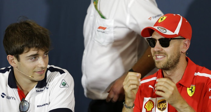 In this May 23, 2018 file photo, Ferrari driver Sebastian Vettel of Germany, right, is flanked by Sauber driver Charles Leclerc of Monaco during a news conference, at the Monaco racetrack, in Monaco. Kimi Raikkonen is leaving Ferrari for Sauber and will be replaced by rookie Charles Leclerc, that will team up with Sebastian Vettel. (AP Photo/Claude Paris)