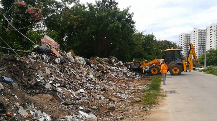 Workers used heavy machinery and hand tools to remove furniture, construction scraps and garbage illegally dumped on the side of the road.