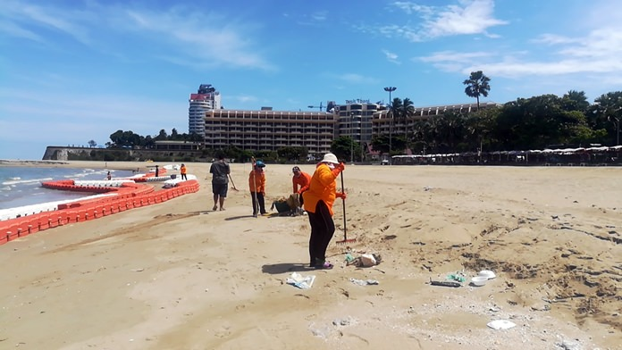 Sanitation workers clean up after a tide of garbage washed up on Pattaya Beach.
